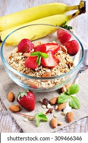 Granola cereal with fresh strawberries, raisins, almonds, and yogurt, muesli for healthy breakfast, morning meal, selective focus