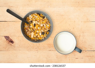 Granola and cereal muesli with dairy milk in a bowl for breakfast on a wooden table