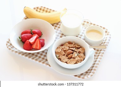 Granola cereal on white bowl with strawberries and banana