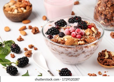 Granola crispy honey muesli with natural yogurt, berries, chocolate and nuts in a bowl against a light background, healthy food, horizontal format