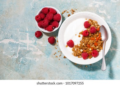 granola with dried apricots, raspberries and yogurt for breakfast, top view horizontal