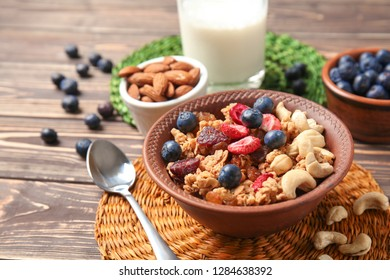 Granola with dried fruits and nuts in bowl on table