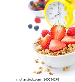 Granola with fresh berries for breakfast and yellow alarm clock on white background close-up