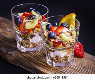 Granola with fresh fruits and jogurt on a wooden board