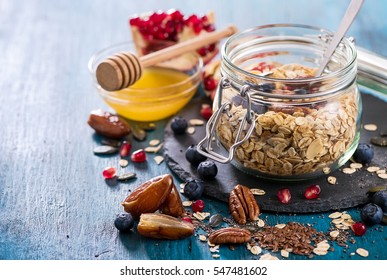 Granola in jar with berries, nuts and seeds, healthy breakfast and diet concept, vitamin snack copy space background