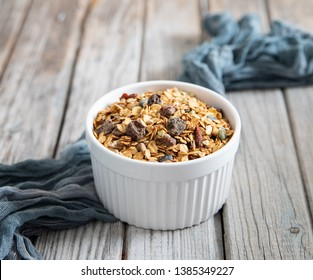 granola lies in a white bowl, gray wooden background