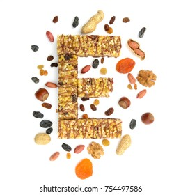 Granola (muesli, cereal) bar in form of letter E and its ingredients. Concept of energy reach healthy food, flat lay
