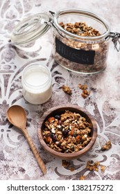 Granola muesli with dried fruits, nuts and seeds and a jar of yogurt for a healthy breakfast
