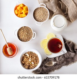 Granola oats and grains breakfast with tea, honey, lemon, mango and milk over white wooden background. Top view
