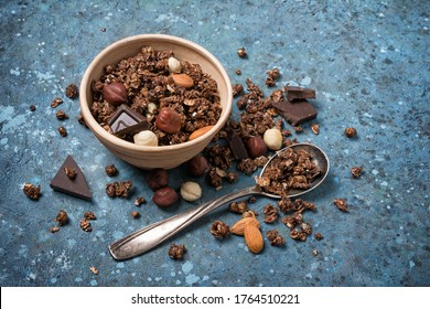 Granola with pieces of dark chocolate, almond and hazelnut in small bowl for nutritious breakfast on blue concrete background