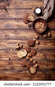Granola served with fugde, chocolate cokies and milk over wooden background. Top view. Copy space
