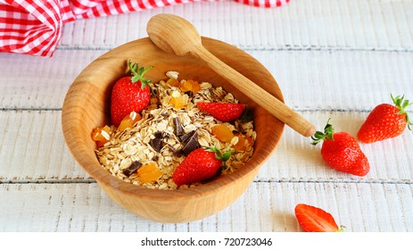 granola with strawberries and chocolate chips on wood, food closeup