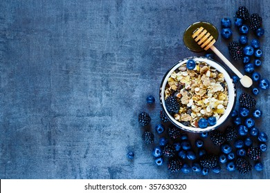 Granola in vintage mug, dark berries and honey for delicious breakfast on grunge background with space for text on left, top view. Organic healthy food and diet concept.