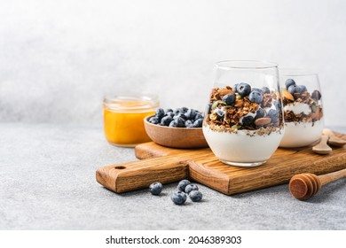 Granola with yoghurt and fresh blueberries in glass. Dessert parfait with berries for breakfast