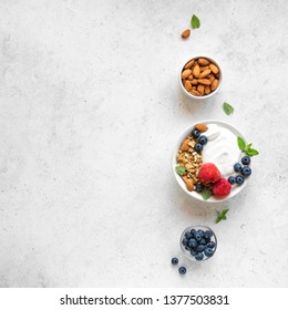 Granola with yogurt and berries for healthy breakfast. Bowl of greek yogurt with granola, almonds, blueberries and strawberries, top view, copy space.