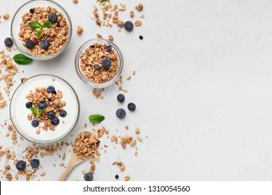 Granola, yogurt, blueberries in bowls on grey background, top view, copy space. Healthy breakfast menu concept. mockup
