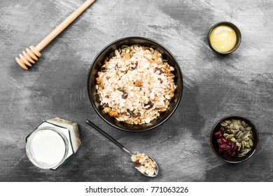 Granola with yogurt, honey, nuts, fruit on a dark background. Top view. Food background