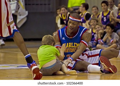 GRANOLLERS, SPAIN - MAY 11:  Hacksaw Hall plays with a child of the public at The Harlem Globetrotters game at Palau d'Esports in Granollers, Catalonia, Spain on May 11, 2012