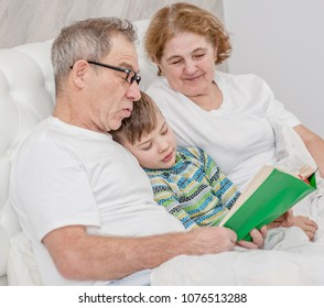 Granparents  read the book to her grandson before going to bed