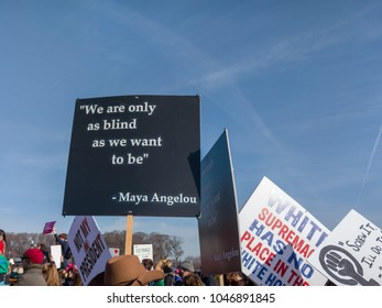 """GRANT PARK, CHICAGO-January 20, 2018. Women's March.  A protester carries a sign with a famous Maya Angelou quote, """"We are only as blind as we want to be."""""""