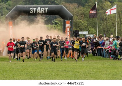Grantham, Leicestershire/UK - May 21, 2016: Participants kick off at the start line through the orange smoke taking on the 2016 Tough Mudder extreme sports charity competition at Belvoir Castle.