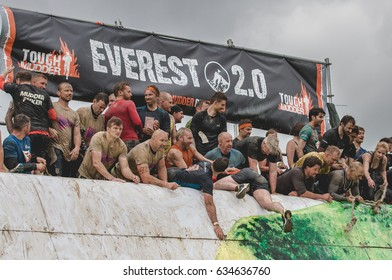 Grantham, Leicestershire/UK - May 21, 2016: Tough Mudders who scaled Everest 2.0 turn lend a hand to other participants at the 2016 Tough Mudder extreme sports charity competition at Belvoir Castle.