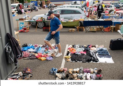 Grantham,United kingdom. 2 June 2019.   Man with blue polo shirt and shorts in the middle of arranged items on the floor to sell at Grantham car boot.