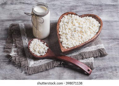 Granulated cottage cheese in a wooden bowl in the form of heart,dairy cream milk jar, burlap background on a light surface
