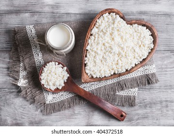 Granulated cottage cheese in a wooden bowl in the form of heart,�dairy cream milk jar, burlap background on a light surface, top view