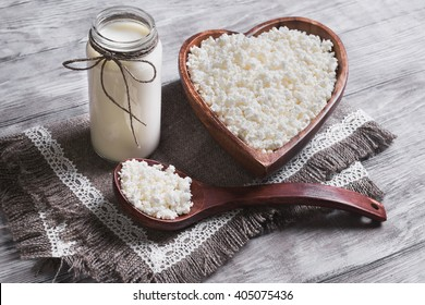 Granulated cottage cheese in a wooden bowl in the form of heart,�dairy cream milk jar, burlap background on a light surface