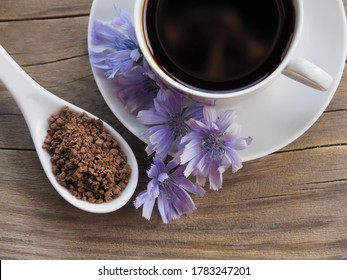 Granulated sublimated chicory in a white spoon, blue flower and chicory drink in a white сup on a wooden background, top view. Healthy natural coffee from the Cichorium plant