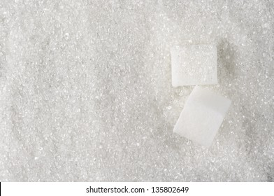 Granulated sugar and sugar cubes as background.