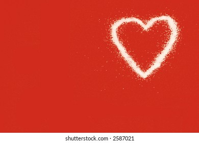 Granulated white sugar in the shape of a heart isolated on red