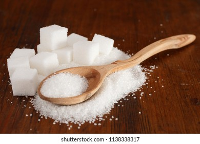 Granulated white sugar in a spoon with some cubes on a brown wooden background potentially for economic news on the price of sugar