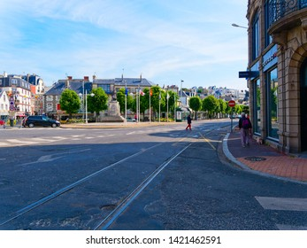 Granville, France - May 23rd 2019: On Place General de Gaulle in Granville A man with a small dog walks towards a crossing while a lady and a dog cross the road.  Cars are parked at the roadside.