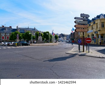 Granville, France - May 23rd 2019: Only a few people are out and abput in the early morning sunshine on Place General de Gaulle in Granville, France. Cars are parked at the roadside.