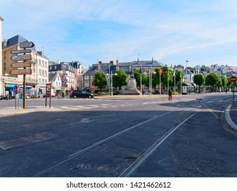 Granville, France - May 23rd 2019: A quite morning on Place General de Gaulle in Granville, France. A lady walks across the road with a dog and cars are parked at the roadside.
