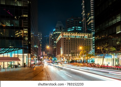 Granville Street in Vancouver, British Columbia, Canada. Summer night on the street of a large modern city with tall houses and moving cars with lighted headlights