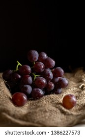 grap,Bunches of fresh ripe red grapes on a wooden textural surface. Ancient style, a beautiful background. Red wine grapes. dark grapes, blue grap,