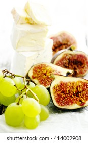 Grape, cheese and figs on a wooden table background.