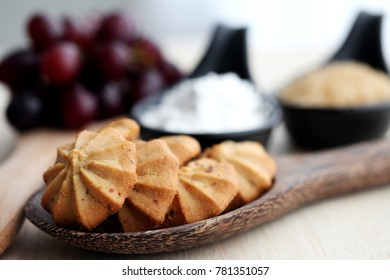 Grape cookies on woodenspoon with sugar , grape ,flour and woodentable background