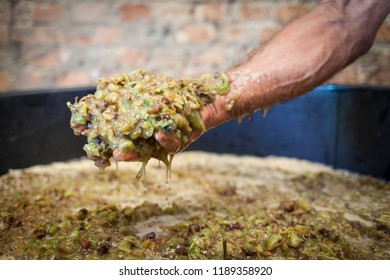 Grape harvest: farmer hands keep grape must