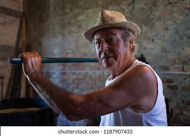 Grape harvest: old winemaker farmer  portrait that working on a vintage wine press