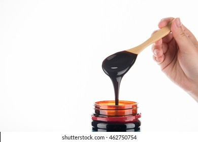 Grape molasses flowing from the spoon on wooden background