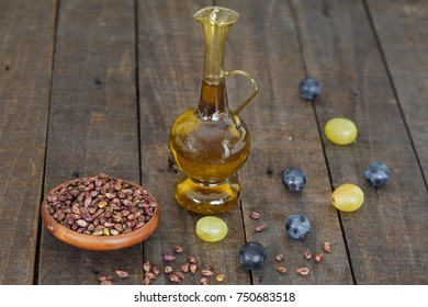 Grape seed oil in a glass jar on wooden background. Healthy, eco product.