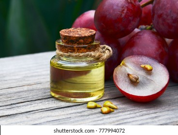Grape seed oil in a glass jar and fresh grapes on old wooden table for spa and bodycare.Spa,Bio,Eco products concept.