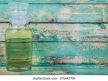 Grape seed oil in glass vial over wooden background
