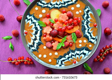 Grapefruit, apricot and white peach smoothie bowl with coconut yogurt swirls and fresh fruit. Top view, purple background.