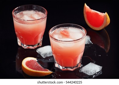 Grapefruit cocktail . Refreshing iced fruit drink on a black background.Selective focus