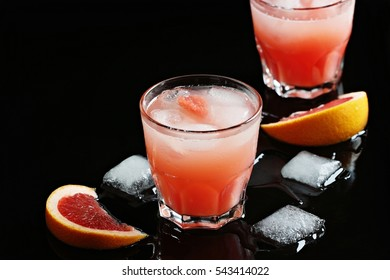 Grapefruit cocktail.Refreshing iced fruit drink on a black background.Selective focus